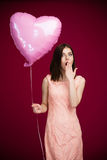 Young woman holding heart shaped balloon and yawning Stock Photography