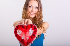 Young woman holding heart shaped box royalty free stock photography
