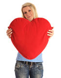 Young woman holding a heart-shaped pillow Royalty Free Stock Images