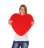 Young woman holding heart-shaped pillow Royalty Free Stock Photo