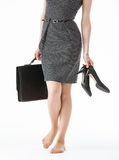 Young woman holding her black shoes and a briefcase Royalty Free Stock Photos