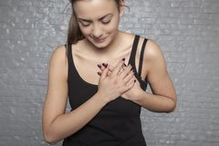 A young woman is holding her chest, Possible heart attack, first. Symptoms front view stock images