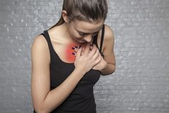 A young woman is holding her chest, Possible heart attack, first. A young woman is holding her chest, Possible heart attack first symptoms royalty free stock images