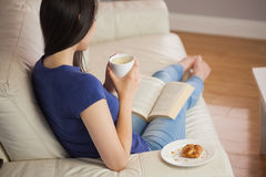 Young woman holding her coffee and reading book Royalty Free Stock Photos