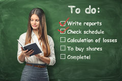 Young woman holding her day planner standing near list of things to do at work written on green chalkboard. A young woman holding her day planner standing near Royalty Free Stock Photos