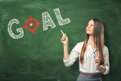 Young woman holding her glasses and pointing finger at word `goal` written on green chalkboard wall. A young woman holding her glasses and pointing the finger Royalty Free Stock Photos