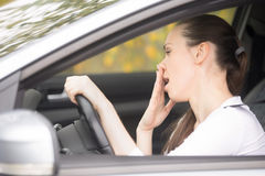 Young woman holding her head at steering wheel Stock Photography