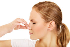 Young woman holding her nose because of a bad smell Royalty Free Stock Photo