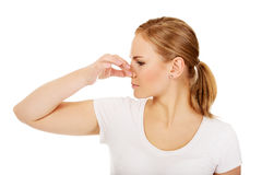 Young woman holding her nose because of a bad smell.  stock photography