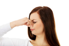 Young woman holding her nose because of a bad smell.  royalty free stock image