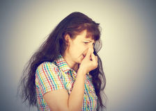 Young woman holding her nose because of bad smell. On a gray background stock photography
