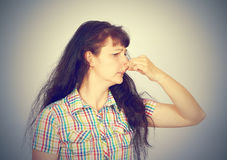 Young woman holding her nose because of bad smell. On a gray background stock image