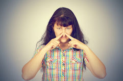 Young woman holding her nose because of bad smell. On a gray background stock photo