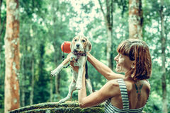 Young woman holding her puppy beagle dog in nature of tropical Bali island, Indonesia. Young woman holding her puppy beagle dog in nature of tropical Bali Stock Images