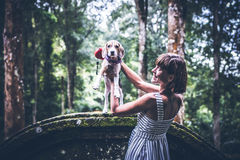 Young woman holding her puppy beagle dog in nature of tropical Bali island, Indonesia. Young woman holding her puppy beagle dog in nature of tropical Bali Stock Photo