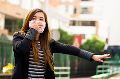 Young woman holding his protective mask with her hand on the street in the city with air pollution, asking for a taxi Royalty Free Stock Images