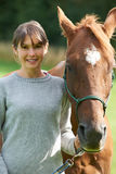 Young Woman Holding Horse In Field Stock Image