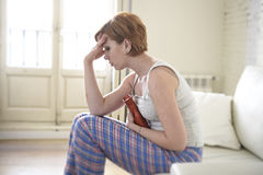 Young woman holding hot water bottle in belly suffering stomach cramp and period pain Stock Photography