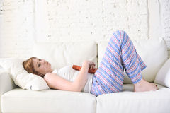 Young woman holding hot water bottle in hurting tummy suffering stomach cramp period pain Royalty Free Stock Images