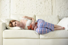 Young woman holding hot water bottle in hurting tummy suffering stomach cramp period pain Stock Photography