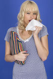 Young Woman Holding a Hot Water Bottle Sneezing with Cold in Pyjamas. Attractive Young Woman Holding a Hot Water Bottle Sneezing with Cold in Pyjamas Royalty Free Stock Photo