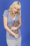 Young Woman Holding a Hot Water Bottle with Stomach Ache Wearing Pyjamas Stock Photography