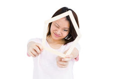 Young woman holding house shaped popsicle sticks on face Stock Image
