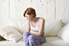 Young woman holding hurting belly suffering stomach cramp period pain. Young beautiful red hair woman holding with her hands a hurting belly suffering stomach Stock Photo