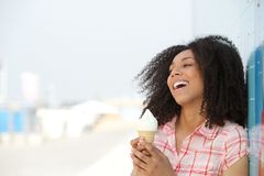Young woman holding ice cream cone. Close up portrait of a beautiful young woman smiling and holding ice cream cone outdoors Royalty Free Stock Photos