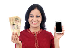 Young woman holding Indian currency and mobile phone. Happy young woman holding Indian currency and mobile phone Royalty Free Stock Photos