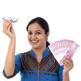 Young woman holding indian currency and toy plane against white Royalty Free Stock Photos
