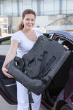 Young woman holding infant safety seat Royalty Free Stock Images