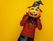 Young woman holding jack-o-lantern pumpkin in front of face Stock Photography