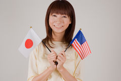 Young woman holding Japanese and American flags. Waist up of young woman holding Japanese flag and American flag Royalty Free Stock Photos