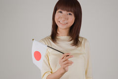 Young woman holding Japanese flag. Young woman smiling with Japanese flag in a hand Stock Photo