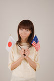 Young woman holding Japanese flag and American fla. Young woman looking at camera with  Japanese flag and American flag in hands Stock Photo