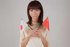 Young woman holding Japanese flag and Chinese flag Royalty Free Stock Photos