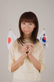 Young woman holding Japanese flag and Korean flag. Young woman looking at camera with  Japanese flag and Korean flag in hands Stock Photos