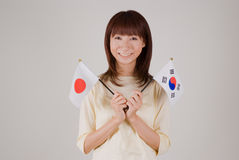 Young woman holding Japanese flag and Korean flag Stock Photography