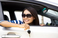 Young woman holding key. In car Stock Photography
