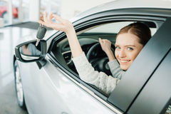 Young woman holding key while sitting in new car Stock Photo