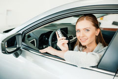 Young woman holding key while sitting in new car Royalty Free Stock Image