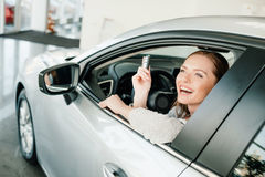 Young woman holding key while sitting in new car Stock Photos