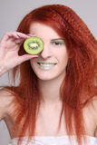 Young woman holding kiwi fruit for her eye Stock Photos