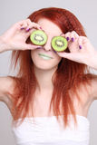 Young woman holding kiwi fruit for her eyes Stock Photography