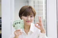 Young woman holding Korean Won with OK sign Royalty Free Stock Photography