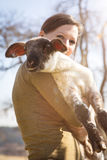 Young woman holding a lamb, animal protecting and loving Royalty Free Stock Photo