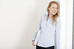 Young woman holding a laptop. Young woman leaning against a white wall holding a white laptop computer stock image