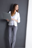 Young woman holding a laptop,  on grey Royalty Free Stock Image