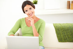 Young woman holding a laptop indoors. Young woman with brown hair holding a laptop while sitting indoors - copy space stock photography